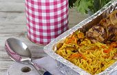 Food in boxes of foil on napkin on wooden board on wooden table