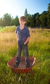 A Real Life Youg Boy Standing In A Wheelbarrow