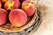 Peaches on wicker tray on sackcloth on wooden table