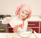 Smiling Little Girl With Chef Hat Put Flour For Baking Cookies