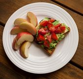 Plate Of Tomato And Avocado On Toast With Apple Slices