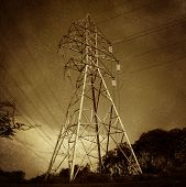 stock photo of hydro-electric  - Electric power tower and electricity distribution network on a grunge vintage texture as a symbol of energy and the electrical grid infrastructure - JPG