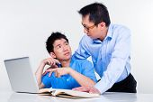 Chinese father helps his son with knowledge and experience for his complex and complicated homework