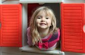 Little blond girl smiling through the window of kids playhouse