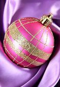 Beautiful Christmas ball on purple satin cloth