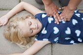 stock photo of resuscitation  - A little girl receiving first aid heart massage by nurse or doctor or paramedic - JPG