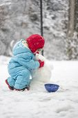 Young Child Building A Snowman