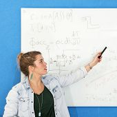 Young woman explaining a complex mathematical calculation in civil engineering she just wrote down on a white board