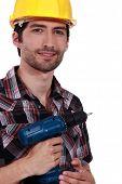 Confident handyman holding drill