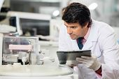 stock photo of scientist  - Male scientist observing experiment in laboratory - JPG