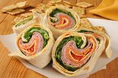 stock photo of sandwich wrap  - Closeup of an Italian meat wrap sandwich with flatbread crackers - JPG