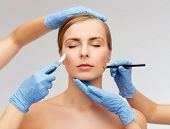 healthcare, beauty and medicine concept - beautiful woman face with closed eyes and beautician hands
