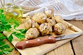 image of jerusalem artichokes  - Whole tubers of Jerusalem artichoke with parsley knife napkin oil on wooden board