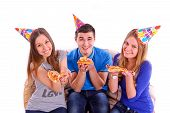 Three Friends Sitting On A Sofa And Eating Pizza