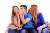 Three Friends Whispering Secrets To Shocked Brunette At Home On Couch Isolated