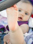 Bare Foot Of Baby Girl  Resting On Stroller