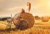 Fashion photo beautiful woman sitting on a bale of wheat next to the old bike