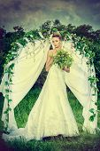 Beautiful elegant bride stands under the wedding arch. Wedding dress and accessories. Wedding decora