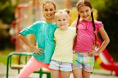 Image of cute girls posing on playground outdoors