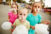 Image of funny girls with cotton candy posing on playground outdoors
