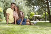 Full length portrait of loving young couple relaxing on grass in park