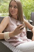 Beautiful young woman with glass of red wine sitting on chair outdoors