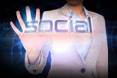 Businesswoman presenting the word social against glowing blue pattern on black background