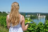 Girl holding wine and grapes against Rhine rive in Rheinau, Switzerland