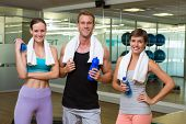 Fit man and women smiling at camera in studio at the gym