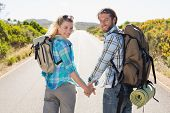 Attractive couple standing on the road holding hands smiling at camera on a sunny day