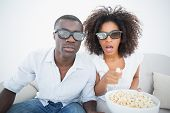Couple sitting on couch together watching 3d movie at home in the living room