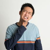 Asian man sore throat with painful face expression, on plain background