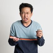Asian male holding medicine bottle while sneezing, on plain background