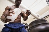 image of muscle builder  - Shirtless body builder scooping up protein powder in gym - JPG