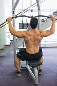 Rear view of a muscular man exercising on a lat machine in gym