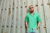 fashion casual man with beard standing with hands in pockets against metal wall
