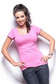 relaxed smiling casual woman standing with hands on hips in studio