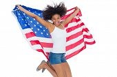 Pretty girl wrapped in american flag jumping and smiling at camera on white background