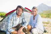 Attractive hiking couple smiling at camera outside their tent on a sunny day
