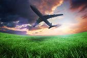 Composite image of airplane taking off against green field under orange sky