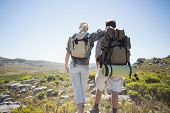 Hiking couple standing on mountain terrain on a sunny day