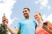 fitness, sport, training, technology and lifestyle concept - two smiling people with smartphones and