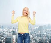 happiness and people concept - laughing young woman with hands up