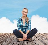 happiness and people concept - smiling young woman in casual clothes sitting on floor