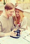 summer holidays and dating concept - smiling couple with photo camera at cafe in the city