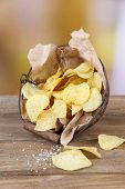 Tasty potato chips in metal basket on wooden table, on light background