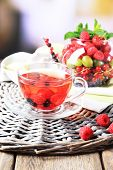 Fruit red tea with wild berries in glass cup, on wooden table, on bright background