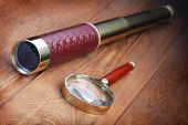 vintage telescope and magnifier on a wooden board