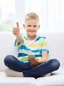 home, leisure, childhood, technology and internet concept - little boy with smartphone showing thumb