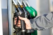 stock photo of gasoline station  - Man holding a fuel nozzle - JPG